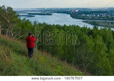 Photographer in red jacket taking photo of Irkutsk city and Angara river from a hill