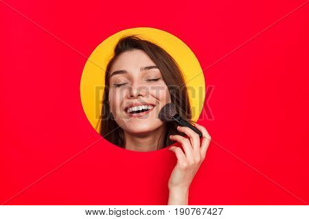 Woman in cut circle applying makeup with brush keeping eyes closed and looking happy.