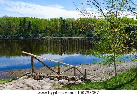 Beautiful view of forest on bank of Western Dvina river with reflection in water. Territory of museum-estate of I.E. Repin