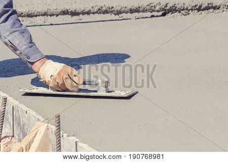 Construction worker leveling concrete pavement outdoors with a trowel.