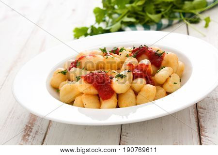 Gnocchi with tomato sauce on white wooden table