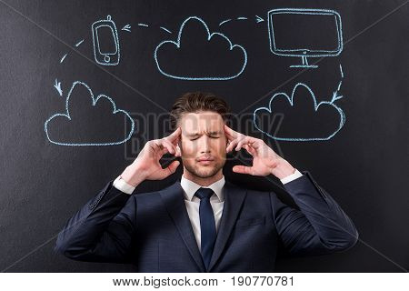 Concept tired from project. Portrait of exhausted young man is massaging his head and feeling headache with illustration of clouds network connection around him