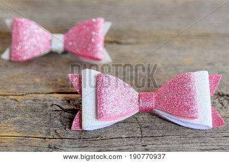 Beautiful hair bows accessories made of pink and white felt with sequins. Hair accessories for girls on a vintage wooden table