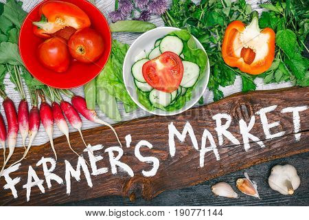 Wooden board with handwritten text 'Farmers market' and variety of fresh vegetable such as tomato, cucumber, bell pepper, raddish, salad, cilantro on wood background. Flat lay