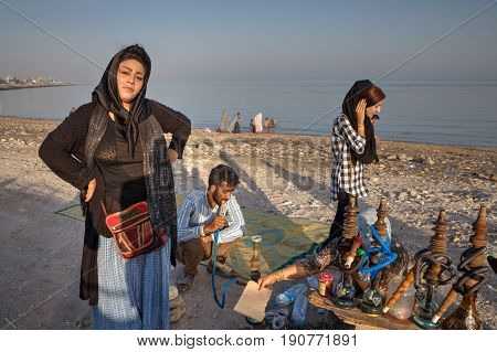 Bandar Abbas Hormozgan Province Iran - 16 april 2017: Portrait of an Iranian woman who is resting on the Persian Gulf beach on a sunny evening near a hookah.