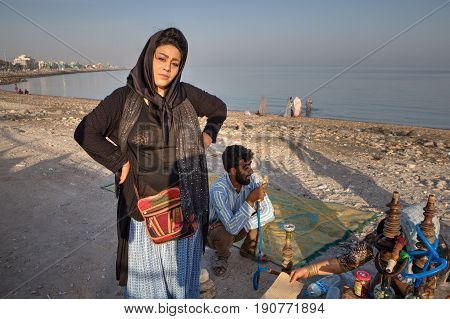 Bandar Abbas Hormozgan Province Iran - 16 april 2017: An Iranian woman wearing a hijab stands near a hookah smoker on a sunny evening on the shore of the Persian Gulf.