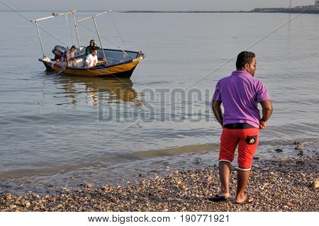 Bandar Abbas Hormozgan Province Iran - 16 april 2017: An Iranian man is standing on the shore to which a pleasure boat with four people aboard is arriving.