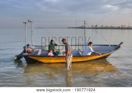 Bandar Abbas Hormozgan Province Iran - 16 april 2017: A motorized pleasure boat with an Iranian family on board stands in shallow water near the shore of the Persian Gulf on a sunny evening.