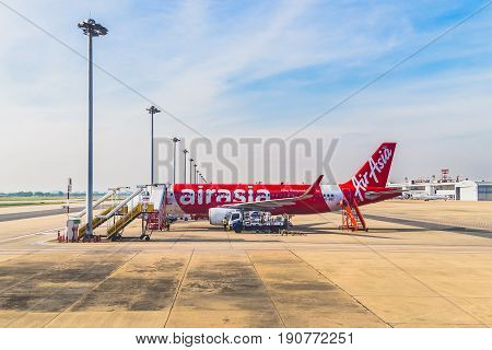 Bangkok, Thailand - December 1, 2016: Airplanes of Air Asia standing on airport Don Mueng in Bangkok. Around are luggage trolleys and a car. At car a man is standing. Behind ladder at back of airplabe are three staffs.