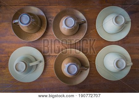 Upside Down Cups of coffee arranged in Rows on wood table