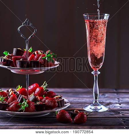 Sparkling pink wine is poured in glass. Stand with strawberries and sweets on a wooden table. Delicious dessert. Atmosphere of luxury and a romantic evening. Selective focus