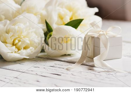 Bouquet of white peonies and present box on the wooden table soft focus background
