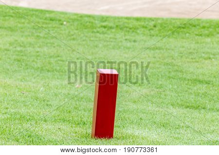 The red distance marker pole to inform range of golfing with blurred green golf course.