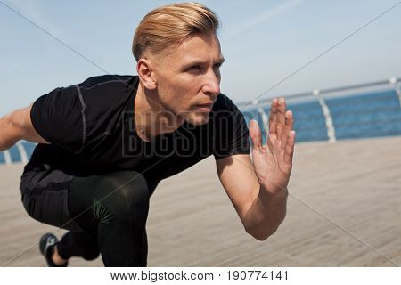 Young sportive man on crouch start ready to run on wooden pier with sea on background.