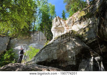 The tourist looks on the white sandstone outcrops. Sietiniezis Rock, Latvia.