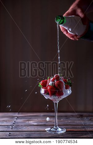 Glass with strawberries on a wooden table. Champagne is poured into a glass with strawberries. Flows and splashes of champagne. Delicious dessert