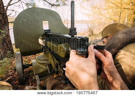 Dyatlovichi, Belarus - October 1, 2016: Reenactors Dressed As Russian Soviet Red Army Soldiers Of World War II Hidden Sitting With Maxim's Machine Gun Weapon In An Ambush In Autumn Forest.