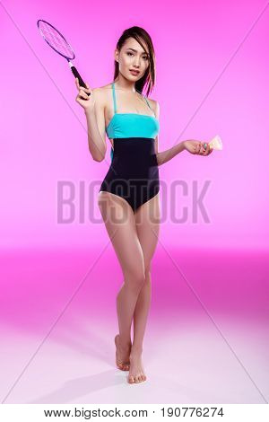 Beautiful Young Woman In Swimsuit Holding Badminton Racquet With Shuttlecock And Looking At Camera