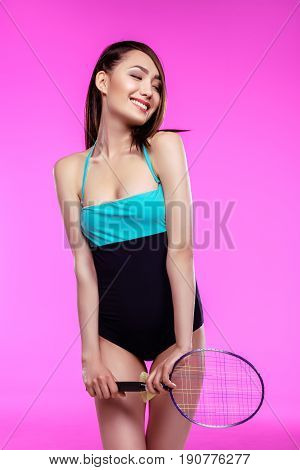 Smiling Young Woman In Swimsuit Holding Badminton Racquet And Shuttlecock Isolated On Pink