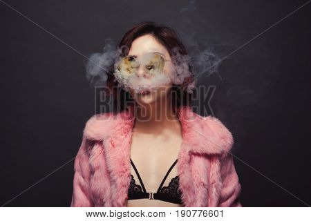 Young brunette in sunglasses and pink fur coat breathing out fumes on dark background.
