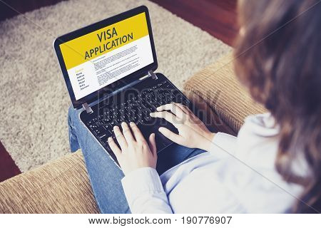 Woman doing electronic Visa Application in a laptop by internet.