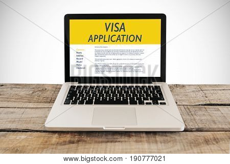 Visa Application form in a laptop computer over a wooden desk.