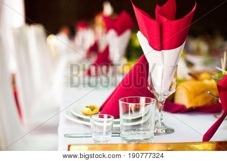White and red serviettes stand in the wineglass on dinner table