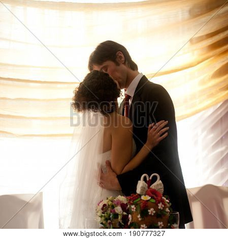 Beauriful Wedding Couple Kisses In The Front Of A Bright Window