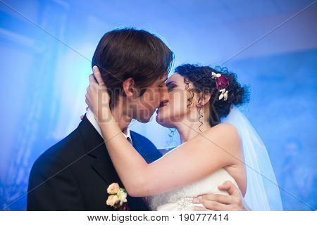 A Look From Below On The Bride Holding Groom's Head Tender During A Kiss On Dancefloor