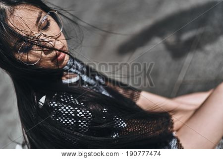 Relaxing in the city. Attractive young woman in casual wear keeping eyes closed while sitting outdoors