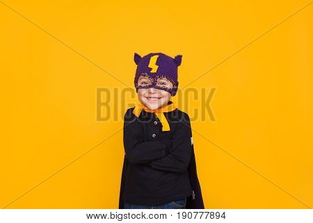 Cheerful adorable boy in knitted mask of superhero posing on yellow background.