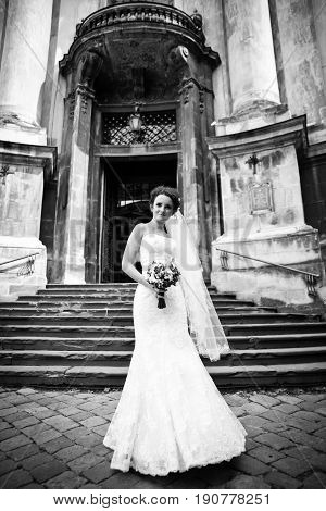 Delicate bride stands beneath an old cathedral in windy weather