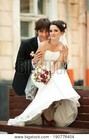 Fiance Holds Bride's Shoulders Tender While They Sit Ovet The Bench
