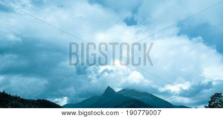 Blue sky in front of a thunderstorm. The pumping atmosphere. Rain clouds. Mountains on the horizon