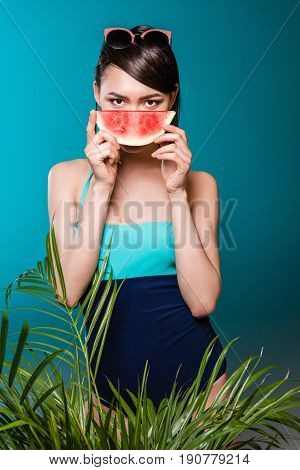 Portrait Of Young Asian Woman In Swimsuit Holding Watermelon Piece In Front Of Face