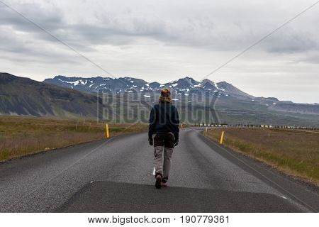 Girl Walking In The Middle Of Icelandic Road With Mountains Covered With Snow On The Horizon. Empty