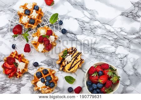 Delicious Belgian Waffles with berry, fruit, whipped cream and different sweet topping on white marble. Top view.