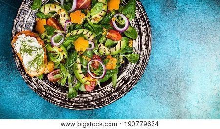 For healthy eating: Salad with grilled avocado, fresh vegetables, toast with soft cheese and mustard dressing. Top view
