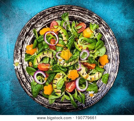 For healthy eating: Salad with grilled avocado, fresh vegetables and mustard dressing. Top view