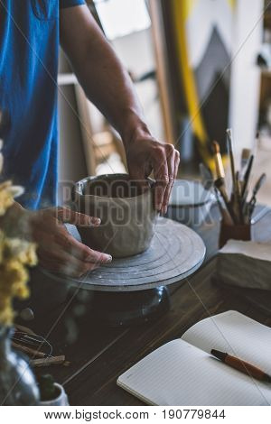 Vertical phone appropriate photo of male artisan hands working on clay pottery in workshop with soft light and hipster objects on the table