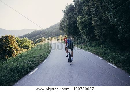 Professional road cyclist on carbon road bike rides towards sunset on forest mountain highway exploring national park looks back in helmet and sport sunglasses