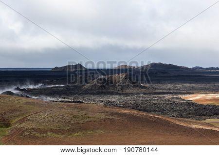 Apocalyptic Smoking Black Landscape Of Krafla Crater. Lava Desert - Still Active Volcanic Area Near