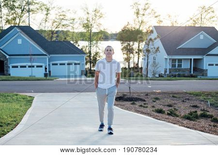 Attractive american teenager in grey sweatpants and white tshirt walks the driveway to a typical residential home on warm summer evening with soft sunset light