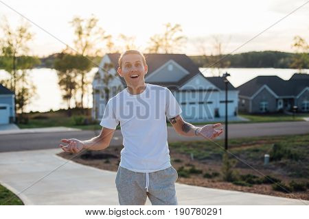 Excited handsome and attractive young american male teenager with healthy white teeth exclaims wow looking into camera in typical american residential neighbourhood