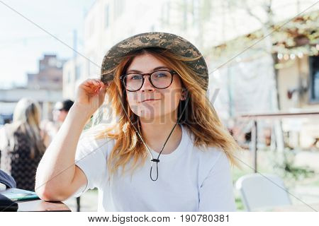 Cute petite female in panama hat and round glasses is ready to explore new horizons and embark on adventure of lifetime during summer spring break vacation