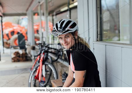 Tired but happy exhausted after long training ride female rider smiles into camera in her helmet and lycra cycling kit with professional road bikes in distance