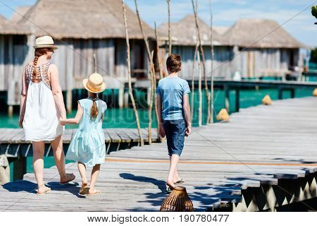 Back view of happy beautiful family walking on wooden jetty during summer vacation at luxury resort