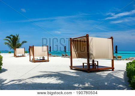 Day bed cabana on a beautiful tropical beach with a palm tree at Maldives
