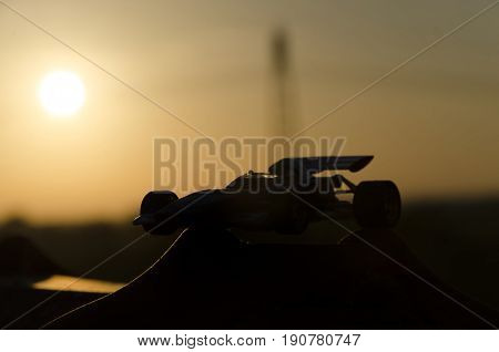 Shape of classic racing car with sunset in background