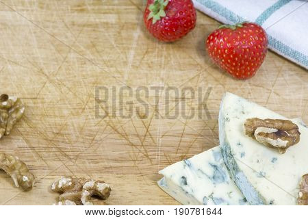 Blue cheese roquefort, strawberries and nuts as background